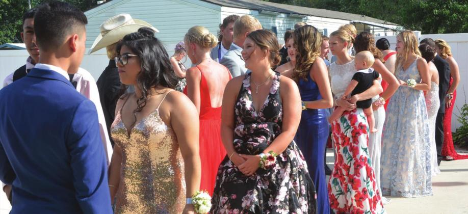 Linn High School students gather in downtown Palmer to start their annual prom on Friday, even though this prom was about three months later than normal.